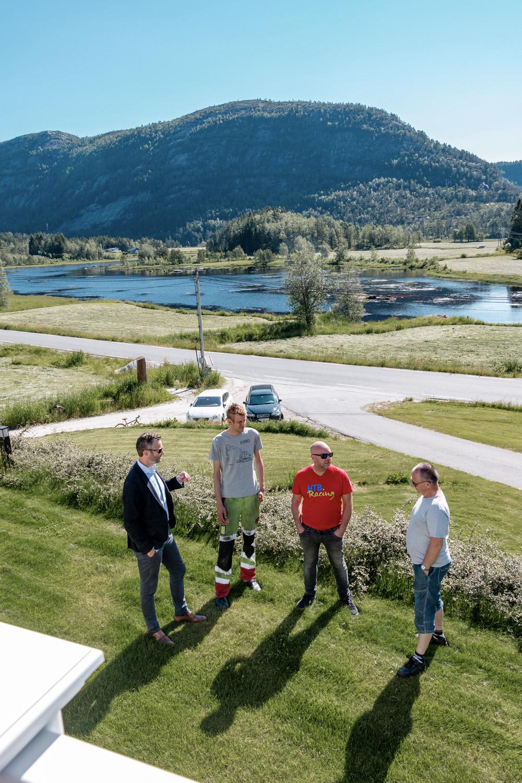 Fire menn står og snakker sammen på en gressplen. Det er sommer og nydelig natur i bakgrunnen.
