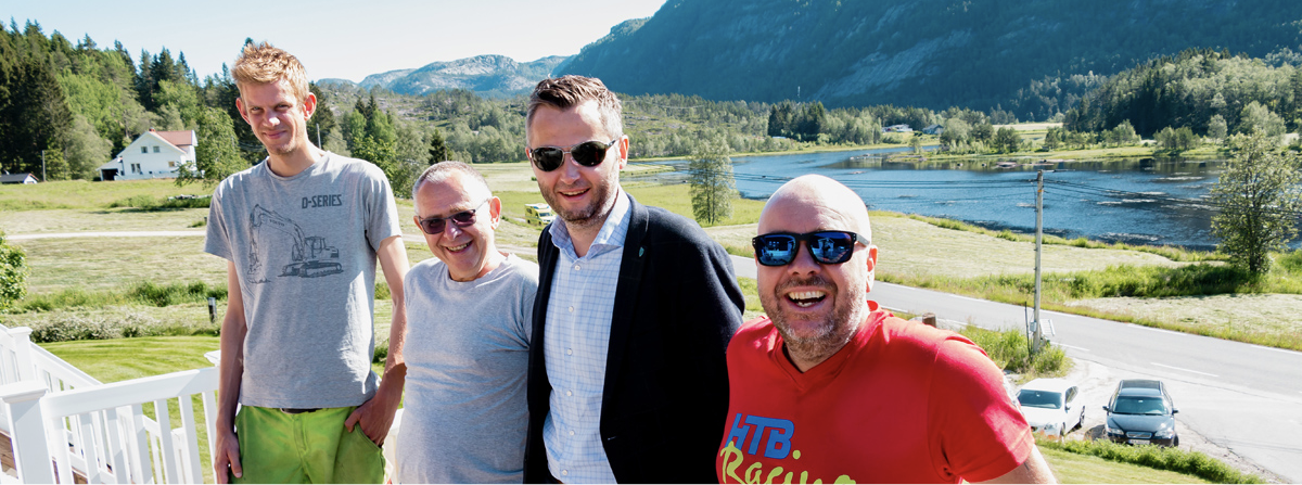 Fire fornøyde karer står på en terasse og smiler til kameraet. Det er et nydelig landskap i bakgrunnen.